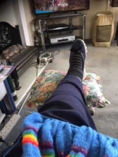 A photo of one leg stretched out on a leg rest, and a piece of colourful knitting on the person's lap. A fireplace and TV in the background.